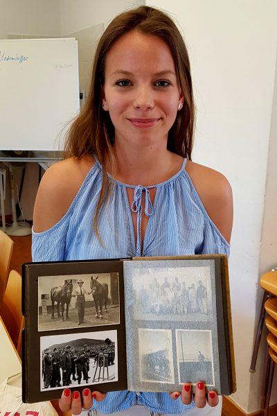 Schülerin mit Fotobuch des Ur-Ur-Großvaters aus dem ersten Weltkrieg